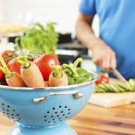 Bowl of fresh vegetables on kitchen counter with senior man working in background. Horizontal shot.